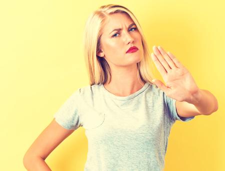 Jonge vrouw die een afwijzing maakt, vormen op een gele achtergrond