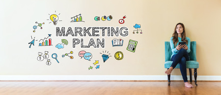 small business: Marketing Plan text with young woman holding a tablet computer in a chair