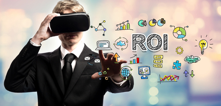 small business: ROI text with businessman using a virtual reality headset Stock Photo
