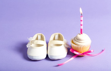 Child celebration theme with a cupcake and baby shoes