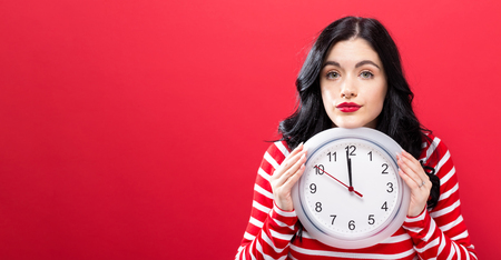 Young woman holding a clock showing nearly 12 Stok Fotoğraf