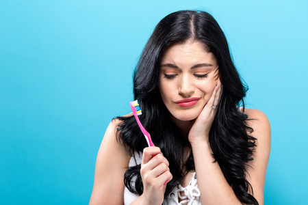 Young woman holding a toothbrush on a solid background
