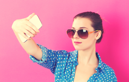 Young woman taking a selfie on a pink background Stock Photo