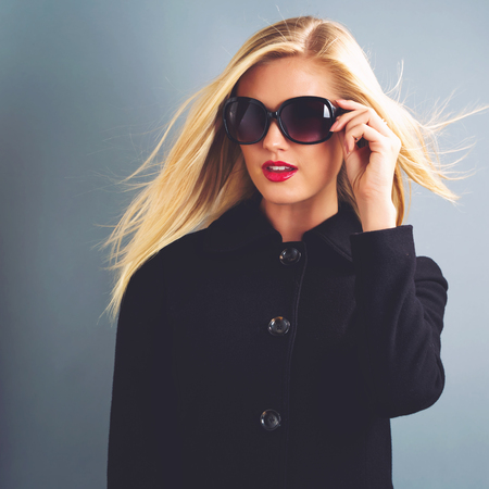 Beautiful young blonde woman in a black coat and sanglasses Фото со стока