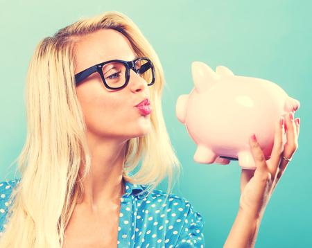 Jonge vrouw met een spaarvarken op een blauwe achtergrond Stockfoto