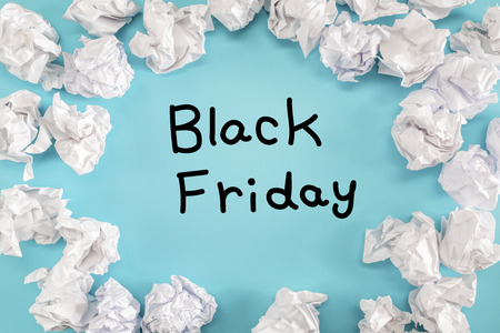 Black Friday text with crumpled paper balls on a blue background Stock fotó