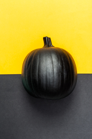 Black pumpkin on a black and yellow split background