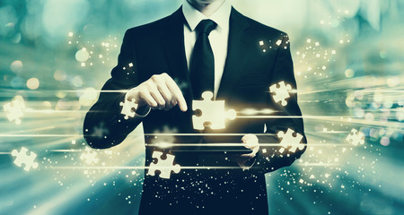 Puzzle pieces with man holding a tablet computer Stock Photo