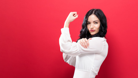 Powerful young woman a solid color background Standard-Bild