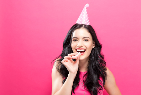 Young woman with party theme on a pink background Stock Photo