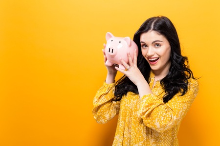 Young woman with a piggy bank on a yellow background Reklamní fotografie