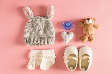 ピンクの背景に赤ちゃんの服やアクセサリー
