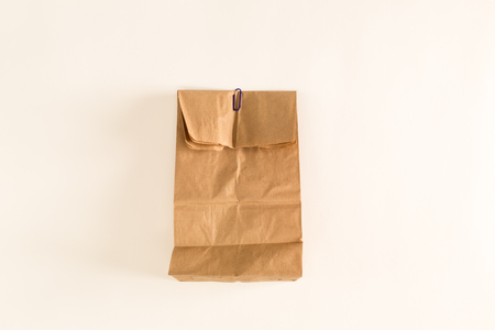 Brown paper bag on an off white background