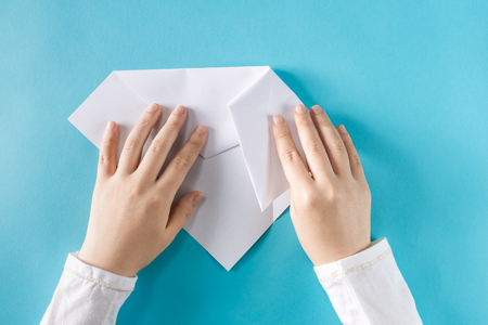 Persons hands folding a paper airplane on a blue background