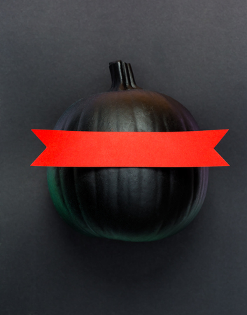 Black pumpkin with red banner on a black background Stock Photo