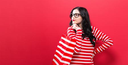 빨간색 배경에 쇼핑 가방을 들고 젊은 여자 스톡 콘텐츠