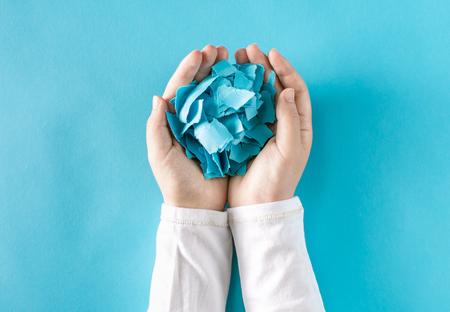 파란색 배경에 구겨진 된 종이 조각을 들고 사람 손 스톡 콘텐츠