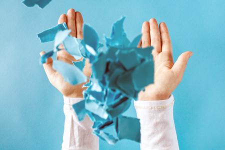 Le mani delle persone gettano pezzi di carta sgualciti nell'aria Archivio Fotografico - 85802925