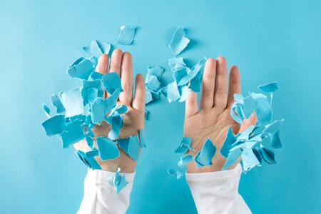 人の手は、空気中にしわの紙の部分を投げる