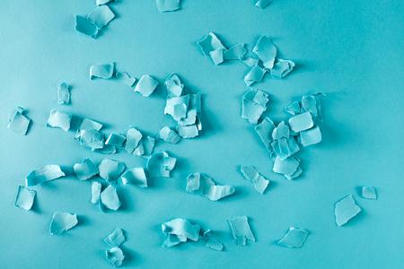 青い背景に散らばった紙の細断