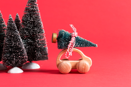 Miniature wooden car carrying a Christmas tree on a red backround Stock Photo