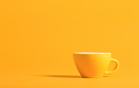 Little yellow teacup on a bright background