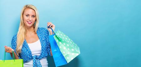青色の背景に買い物袋を持って幸せな若い女
