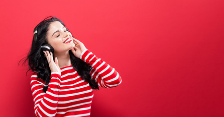 Happy young woman with headphones on a red background