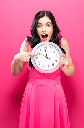 Young woman holding a clock showing nearly 12 Reklamní fotografie