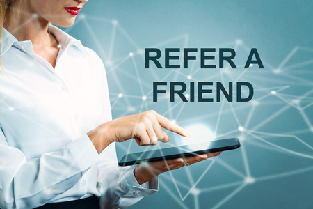 Refer A Friend text with business woman using a tablet Stock Photo