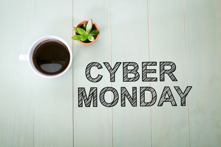 Cyber Monday text with a cup of coffee on a pastel green wooden table