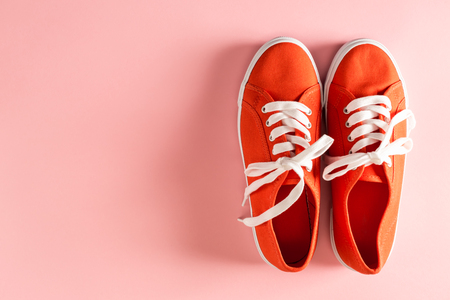 Classic red sneakers on a pale pink background