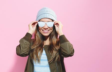 Fashionable girl wearing sunglasses and hat on a pink background