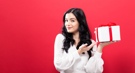 Happy young woman holding a gift box on a solid background