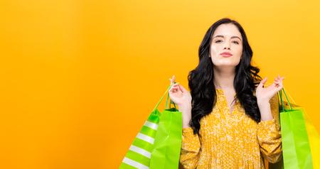 単色の背景上の買い物袋を持って幸せな若い女