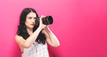 ピンクの背景にカメラを保持している若い女性 写真素材