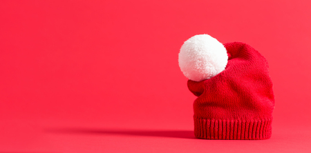 Knit winter hat on a red background