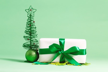 Present box with bauble Christmas ornaments on a green background Stock Photo
