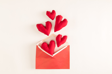 Heart shaped cushions coming out of a gift envelope - love and Valentines Day theme Stok Fotoğraf