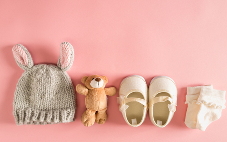 赤ちゃんの服やアクセサリー、ピンクの背景に 写真素材