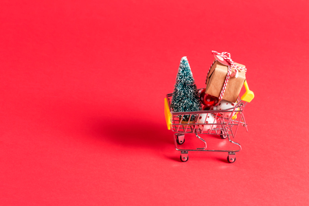 Holiday shopping theme with shopping cart filled with giftboxes