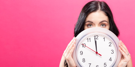 Young woman holding a clock showing nearly 12