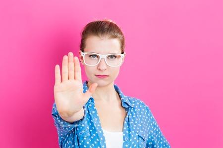 ピンクの背景にポーズの拒絶を作る若い女性