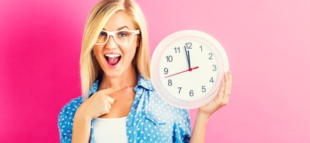 Young woman holding a clock showing nearly 12 Banco de Imagens