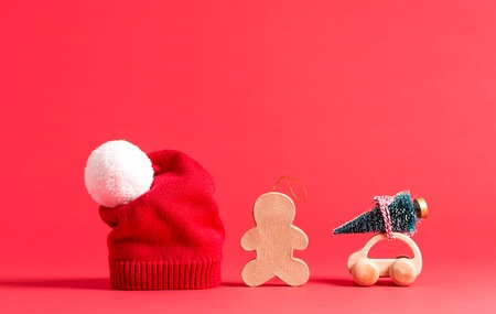 Knit winter hats with Christmas decorations on a red background