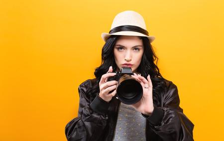 黄色の背景にカメラを保持している若い女性