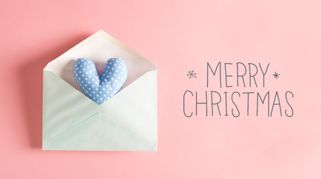 Merry Christmas message with a blue heart cushion in an envelope