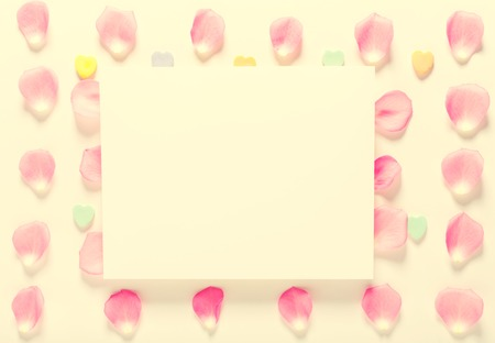 Rose petals and blank white message card aligned on a white background