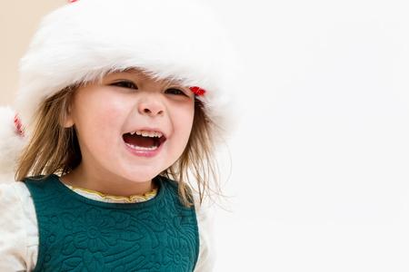 Happy Toddler gir playing in a Santa hat