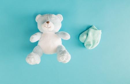 bébé ours en peluche et chaussettes sur un fond bleu